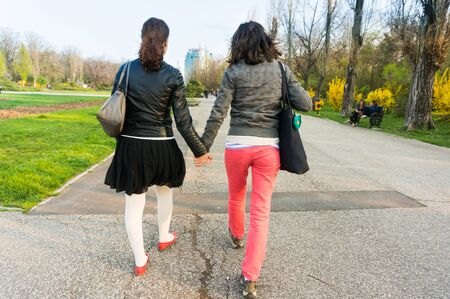 holding hands while walking: Back of two women holding hands while walking in park