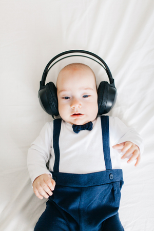 Serious baby boy wearing headphones and listening to music