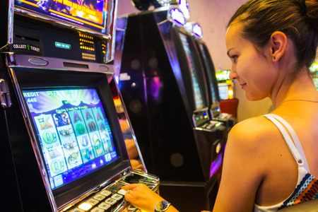 machines: LAS VEGAS - JULY 13, 2013: Woman playing slot machines in The Quad Resort and Casino.