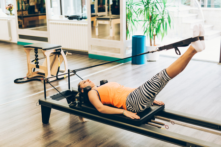 reformer: Woman stretching in a pilates reformer, close-up