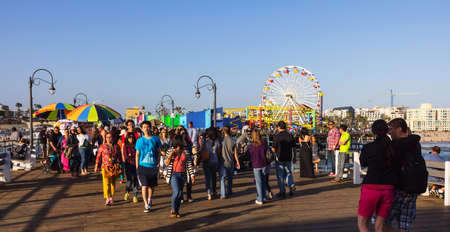 peer: Los Angeles, CA, USA - July 6, 2013: Groups of tourists visiting Pacific Park on Santa Monica peer. Ferris Wheel in the background.