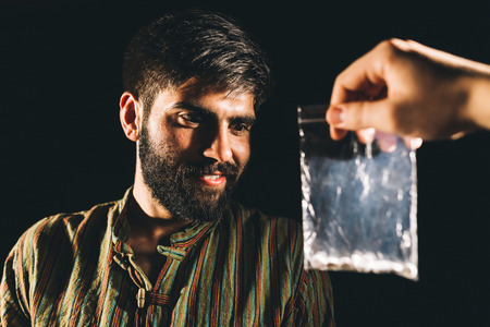drug dealer: Drug dealer giving a packet of heroin or cocaine to a drug addicted Stock Photo