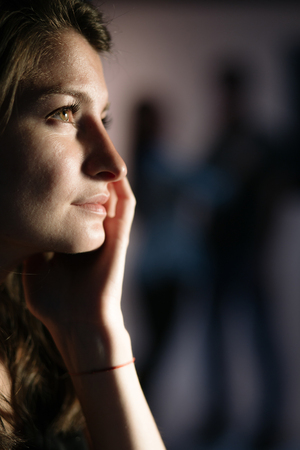 hopefulness: Young thoughtful woman is dreaming of a loving relationship - couple silhouettes on the background