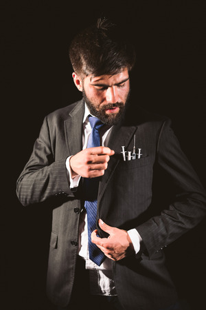 ravaged: Businessman and drug addict choosing a syringe from his pocket Stock Photo