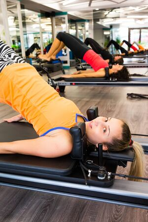 reformer: Pilates  woman in reformer device doing butt exercise