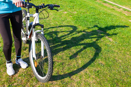 woman shadow: Shadow of a woman and her bike in the park