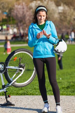 oil park: Woman with oil on her hands after fixing bike in the park Stock Photo