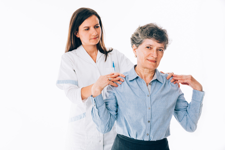 orthopedist: Female orthopedist stretching with care shoulders of a senior patient - isolated on white background
