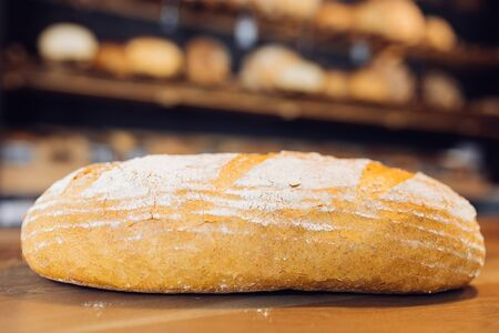 unsliced: Closeup of a fresh loaf with wheat ears  in a bakery