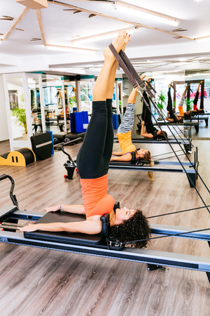 reformer: Young woman doing the shoulder stand on a reformer bed Stock Photo