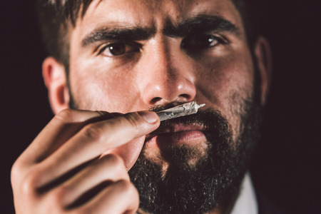Man smelling a joint before smoking it