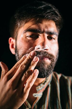 addicted: Drug addicted man having cocaine on his face. Chiaroscuro photography,