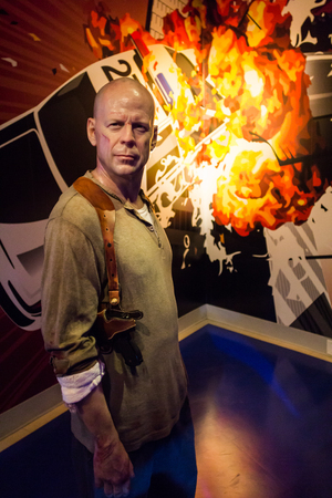 willis: Los Angeles, CA, USA - July 6, 2013: Madame Tussauds Hollywood figures - Bruce Willis. On background exploding police vehicle.