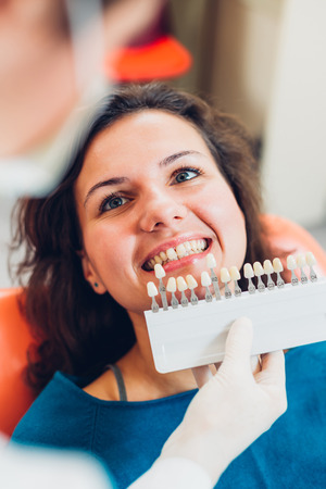 determining: Dentist using shade guide for determining teeth color. Stock Photo