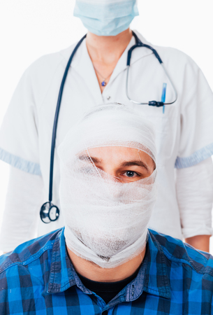 mentally ill: Portrait of a bandaged man with a head trauma and a doctor against him Stock Photo