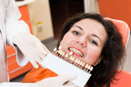 Smiling patient and dentist determinating tooth color with help of a shade guide Stock Photo