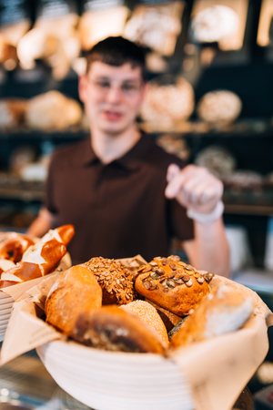 breadbasket: Blurry pose of breadbasket full of buns and a salesman behind. Focus on the buns