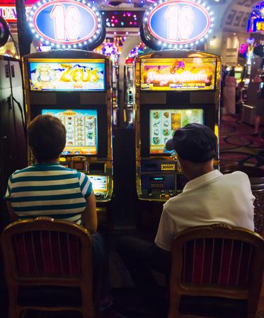 tragamonedas: LAS VEGAS, NV, EE.UU. - 13 de julio, 2013: Pares ocupados jugando las máquinas tragaperras en un casino del hotel. Editorial
