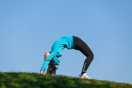 arching: Young woman wearing sports clothes is arching her back in the park
