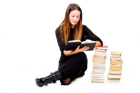 lecturing: Concentrated woman lecturing a book and holding her hand on a pile of books - isolated on white. Stock Photo