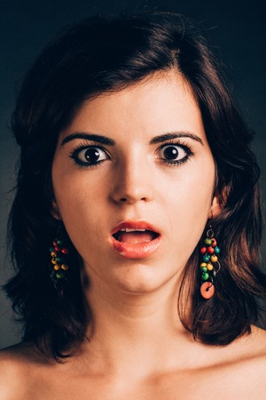 mouth opened: Portrait of a young  shocked woman having mouth opened - isolated on black. Stock Photo
