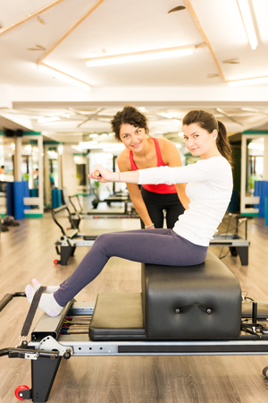 reformer: Woman exercising with the help of a female trainer