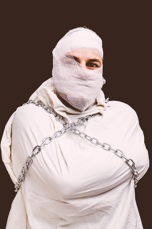 insane insanity: Bandaged patient in straitjacket and chains , sepia version