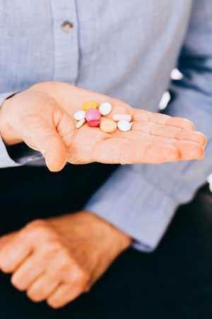 ingestion: Suicidal intentions of a unknown person holding colored pills in hand