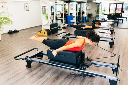 reformer: Women working out in a pilates gym