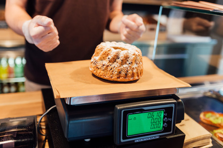 weighting: Baker weighting a pastry cake