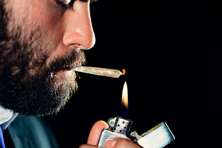 drug dealers: Man lighting and smoking a joint Stock Photo