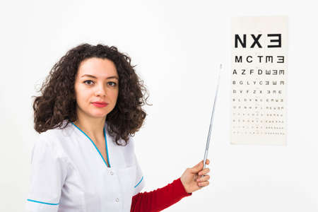 Young doctor testing eyesight with medical instruments - isolated on white.