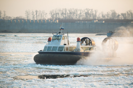 blows: Photo of Russian ACV Hovercraft in Action on a Frosen River. Air Cushion Vehicle Blows Water on a Winter Lake
