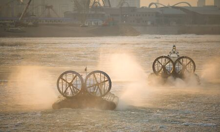 hovercraft: Photo of Two Russian ACV Hovercraft in Action on a Frosen River. Air Cushion Vehicle Blows Water on a Winter Lake