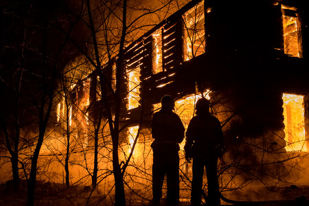 Photo of Firemans Trying to Safe House on Fire. Firefighter Emergency Extinguish Water on Big Old Wooden House on Fire