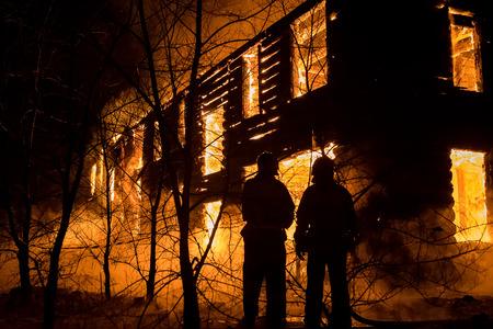 Foto de Firemans tentando esconder em casa. Bombeiro de emergência extinguir a água na grande casa de madeira velha em chamas Foto de archivo