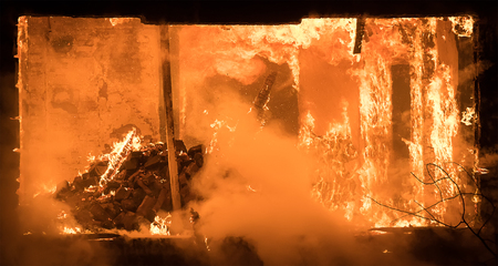 Hot house: Photo of Part of a House on Fire. Window view to Fire Inside Wooden Old House