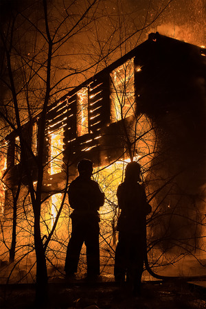 Hot house: Photo of Fireman Trying to Safe House on Fire Stock Photo