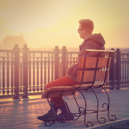 romantic man: Lonely Man Sitting on a Bench during Sunset. Young Man Sitting on Wooden Bench. Sunset Male Outdoor Background