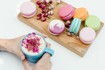 Morning french macarons on wood desk on woman hands holding cup of cappuccino with roses petals Stock Photo