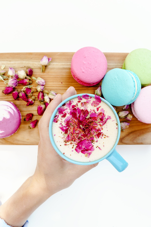 Girl hand hold a blue cup of morning aroma cappuccino. French macarons and roses petals on wood desk.