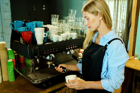 makes: Professional barista girl makes fresh coffee for people in coffeehouse. Stock Photo