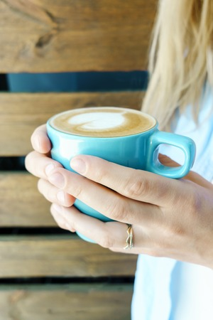 upper leg: Closeup view on blue cup of cappuccino holding by young girl in jeans wear. Wooden background.