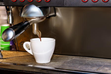 Professional espresso coffee machine makes fresh coffee and pouring it into white cup.