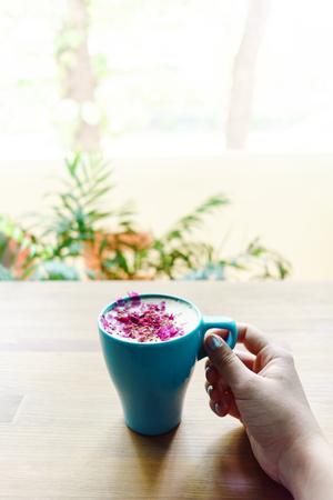 Aantrekkelijke meisjeshand die een kop van cappuccino op houten lijstachtergrond houden. Zomer positiviteit lifestyle. Stockfoto