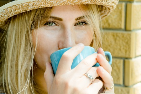Pretty blonde hair beautiful girl happy looking into a camera and holding a cup of cappuccino in hands.