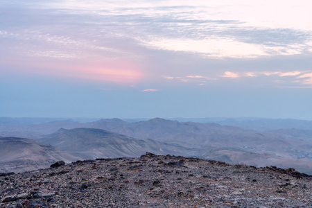 Landscape of magic sunrise over israel judean desert. Morning sky, clouds and sun, mountains and ruins, infinite nature on holy land.