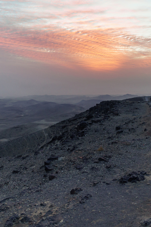 Vertical photo magic sunrise dawn over holy land judean desert in Israel. Landscape with beautiful red sun and blue clouds. Road to infinite violet land. Nobody on photo. Stock Photo