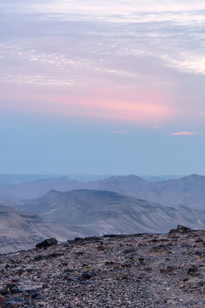 Vertical photo landscape of magic sunrise over israel judean desert. Morning sky, clouds and sun, mountains and ruins, infinite nature on holy land. Stock Photo
