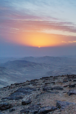 Vertical photo magic landscape of judean desert in Israel. Outdoor sunlight and sunrise over holy land. Mountains, rocks and yellow red blue violet clouds